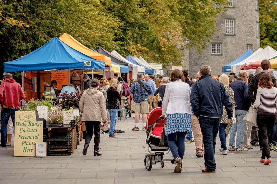 The Kilkenny Farmers Market with Kilkenny Castle as a backdrop.